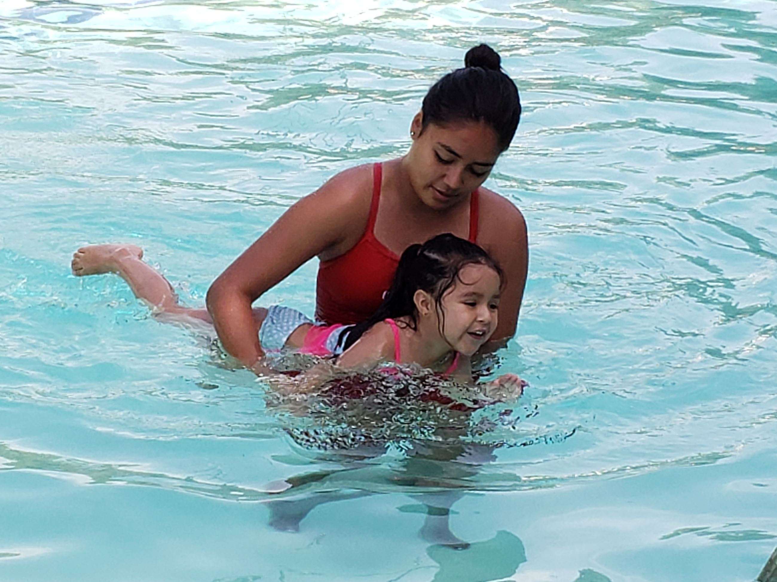 Swim lesson instructor with girl in pool